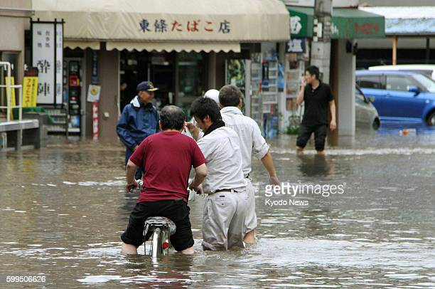 KUMAMOTO Japan People wade through a flooded street in Kumamoto in southwestern Japan on July 12 2012 Recordsetting rainfalls have caused flooding...