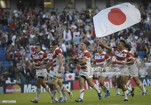 Japan players celebrate winning the Pool B match of the 2015 Rugby World Cup between South Africa and Japan at the Brighton community stadium in...