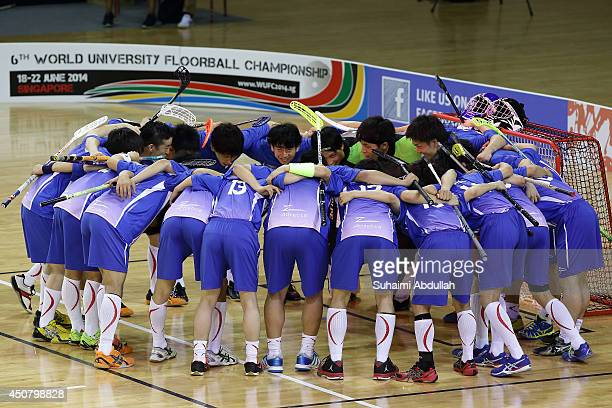 Japan players huddle at the start of their game during the World University Championship Floorball match between Japan and Finland at the Sports Hub...