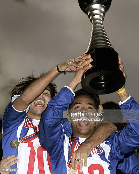 Portugese football club FC Porto midfielder Carlos Alberto holds the Toyota Cup high with his team mate Quaresma in jubilation after winning the...