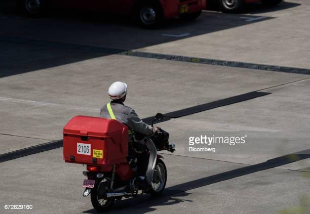 A Japan Post Co employee rides a motorcycle at a post office in Kawasaki Kanagawa Japan on Tuesday April 25 2017 Japan Post Holdings Co Ltdwill book...