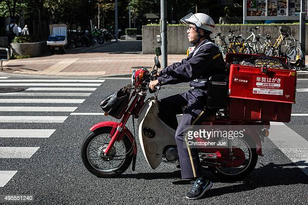 Japan Post Co mail carrier on a motorcycle is seen along a road in downtown Tokyo on November 4 2015 in Tokyo Japan Shares in Japan Post with its...