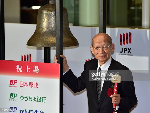 Japan Post Holdings president Taizo Nishimuro rings a bell during the ceremony for the company's listing at the first sector of the Tokyo Stock...