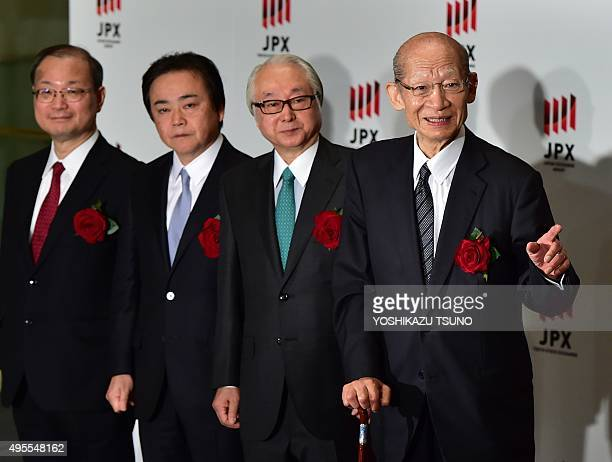Japan Post Holdings president Taizo Nishimuro standssmiles with subsidiary companies Masatsugu Nagato of Japan Post Bank Masami Ishii of Japan Post...