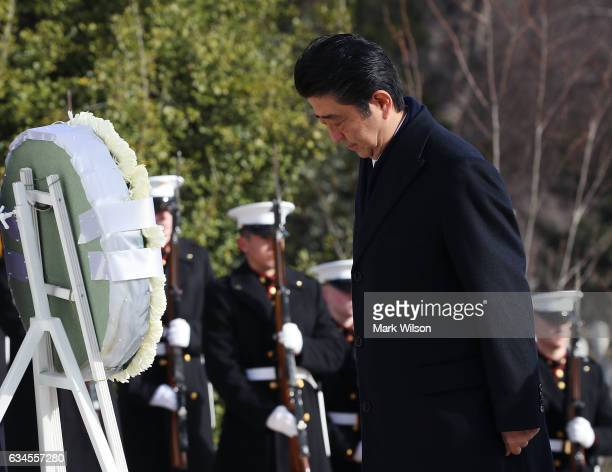 Japan Prime Minister Shinzo Abe pays his respects after laying a wreath at the Tomb of the Unknowns at Arlington National Cemetery on February 10...