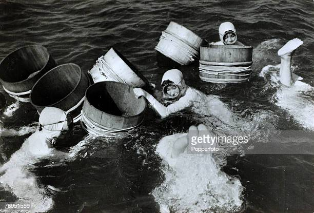 1959 Japanese girl divers who collect oysters from the sea and river estuaries working to collect the cultured pearls