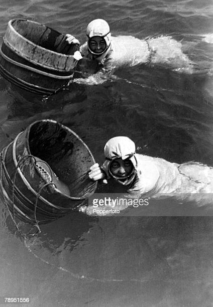 circa 1950 Japanese girl divers who collect oysters from the sea and river estuaries with the containers in which oysters which hold the cultured...