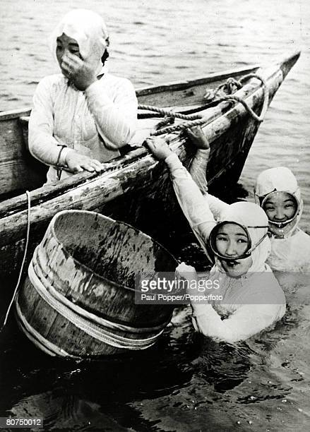 circa 1950 Japanese girl divers who collect oysters from the sea and river estuaries pictured at work with the containers in which oysters which hold...