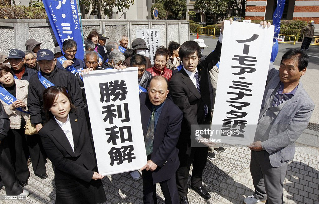 KUMAMOTO Japan Representatives of plaintiffs and others raise banners to celebrate a settlement of a damages suit filed by Minamata disease sufferers...