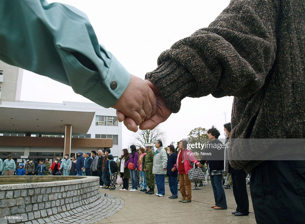NATORI Japan Residents of Natori Miyagi Prefecture hold hands as they await the time of 246 pm on April 11 the exact moment a historic earthquake...