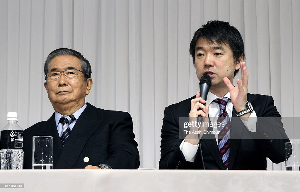 Japan Restoration Party acting president <a gi-track='captionPersonalityLinkClicked' href=/galleries/search?phrase=Toru+Hashimoto&family=editorial&specificpeople=4847016 ng-click='$event.stopPropagation()'>Toru Hashimoto</a> speaks while their president <a gi-track='captionPersonalityLinkClicked' href=/galleries/search?phrase=Shintaro+Ishihara&family=editorial&specificpeople=665335 ng-click='$event.stopPropagation()'>Shintaro Ishihara</a> listens during their campaign pledge announcement press conference on November 29, 2012 in Tokyo, Japan. Japanese vote in the general election on December 16.