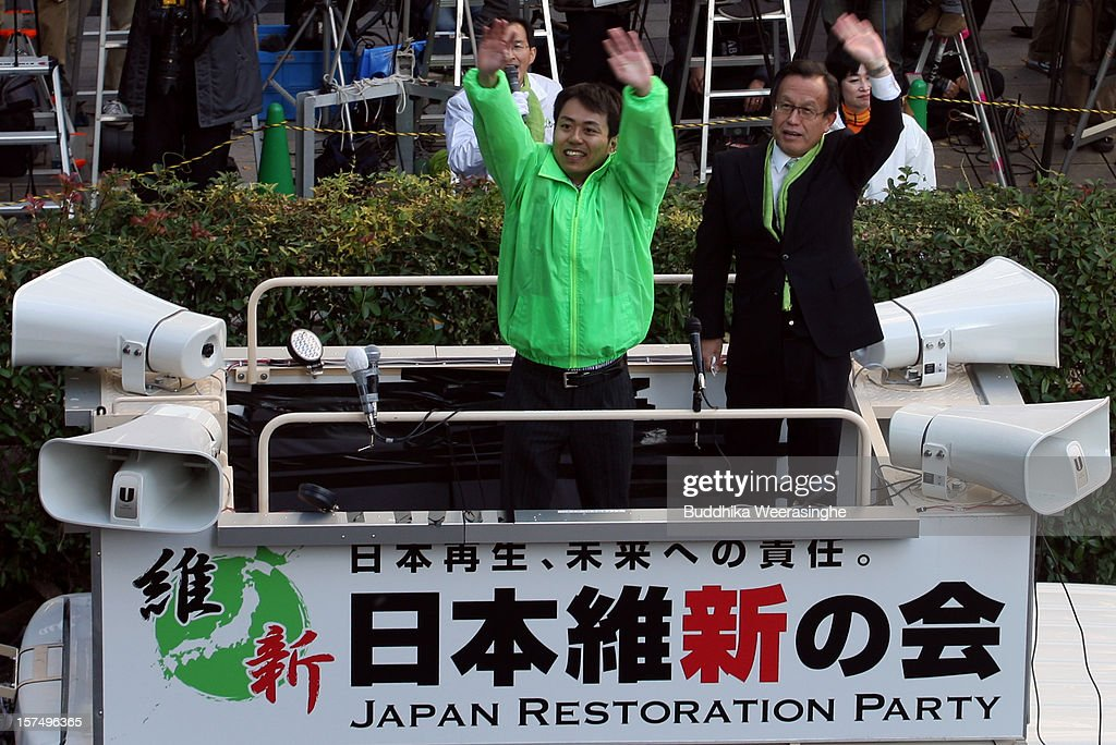 Japan Restoration Party candidate Masatoshi Murakami waves to voters from the roof of a campaign car during his official election campaign for the upcoming lower house election on December 4, 2012 in Osaka, Japan. Japanese vote in the general election on December 16.