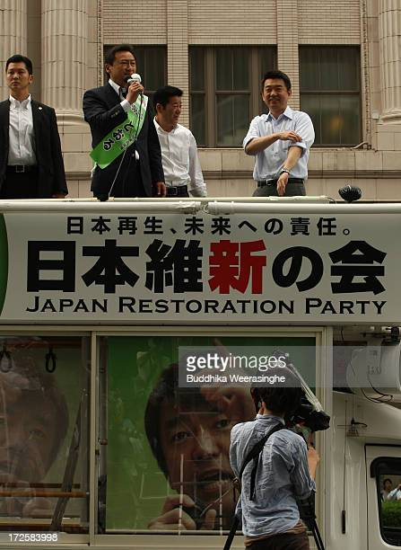 Japan Restoration Party deputy leader Osaka Mayor Toru Hashimoto listens to his party candidate Umemura Satashi speaches which was made from the roof...