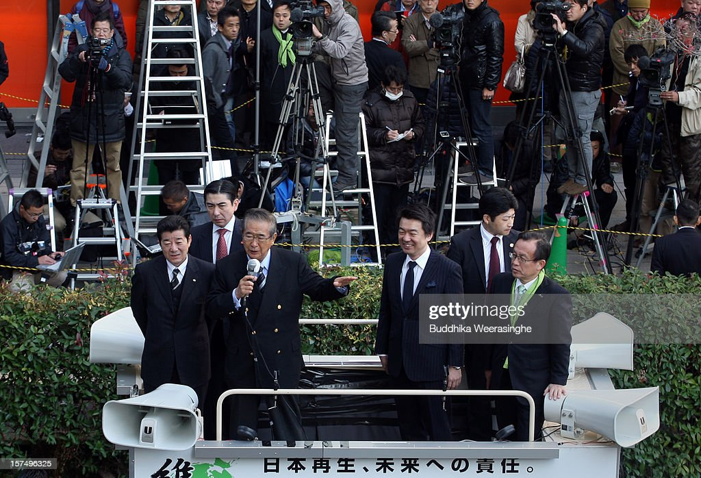 Japan Restoration Party leader former Tokyo Govener Shintaro Ishihara (3rd L) speaks to voters as deputy leader Osaka Mayor <a gi-track='captionPersonalityLinkClicked' href=/galleries/search?phrase=Toru+Hashimoto&family=editorial&specificpeople=4847016 ng-click='$event.stopPropagation()'>Toru Hashimoto</a> (3rd R) looks from the roof of a campagin car during their official election party campaign for the upcoming lower house election on December 4, 2012 in Osaka, Japan. Japanese vote in the general election on December 16.