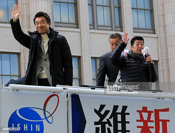 Japan Restoration Party leader Osaka Mayor Toru Hashimoto waves to suppoters as Osaka governor Ichirou Matsui and candidate Inoue Hidataka look on...