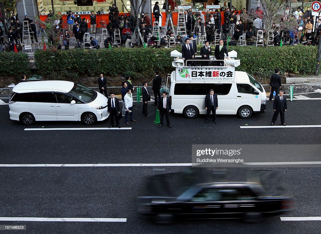Japan Restoration Party members speak to voters from a campagin car during an official election party campaign for the upcoming lower house election on December 4, 2012 in Osaka, Japan. Japanese vote in the general election on December 16.