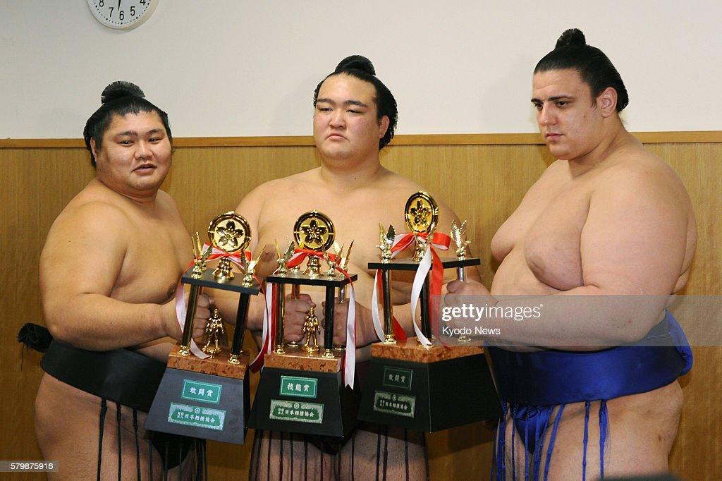 FUKUOKA Japan Sekiwake Kisenosato holds the Technique Prize trophy while rankandfilers Wakakoyu and Aoiyama each hold Fighting Spirit prize trophies...