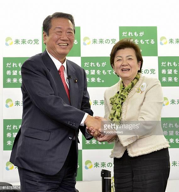TOKYO Japan Shiga Gov Yukiko Kada leader of the Tomorrow Party of Japan and Ichiro Ozawa leader of the People's Life First party shake hands after...