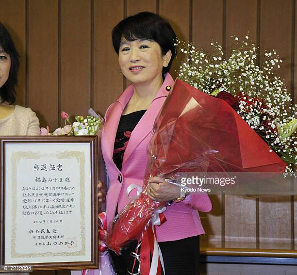 TOKYO Japan Social Democratic Party leader Mizuho Fukushima is pictured with a bouquet of flowers and a framed certificate of her reelection as...