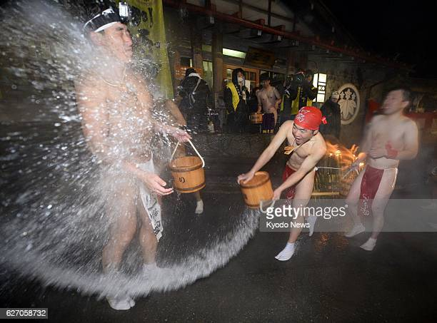 NAGANOHARA Japan Some 60 nearnaked men ranging from teenagers to those in their 50s splash each other with hot water while cheering in the predawn...
