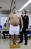 TOKYO Japan Stablemaster and former yokozuna Takanohana measures the height of a Nippon Sport Science University senior at Tokyo's Ryogoku Kokugikan...