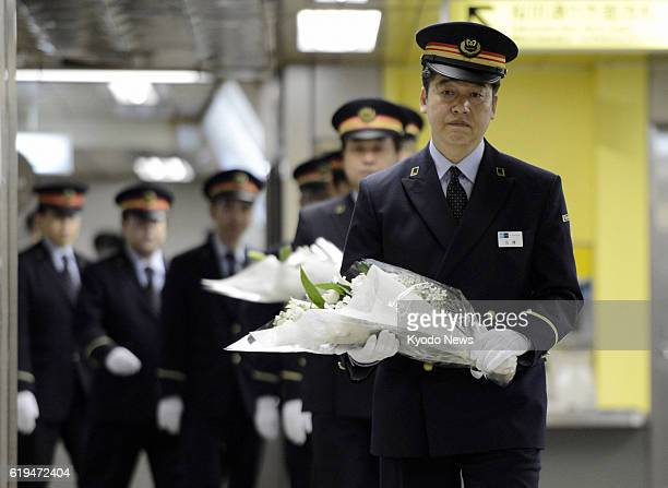 TOKYO Japan Stationmaster Kiyoji Sato heads to offer a bouquet during a ceremony at Kasumigaseki subway station in central Tokyo on March 20 2013 A...