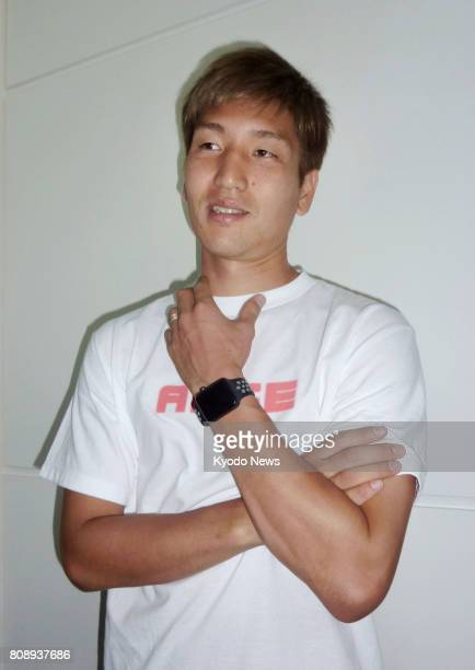 Japan striker Genki Haraguchi meets with reporters on July 5 at Tokyo's Haneda airport before leaving for Germany to join up with Bundesliga club...