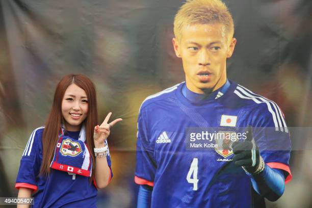 A Japan supporter poses next to an image of Keisuke Honda as she arrives for the Kirin Challenge Cup international friendly match between Japan and...