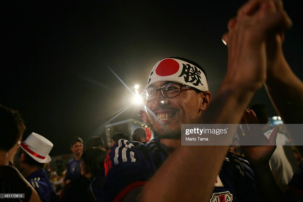 Japan supporters celebrate after their first goal against Colombia while watching at the FIFA Fan Fest on Copacabana Beach on June 24, 2014 in Rio de Janeiro, Brazil.