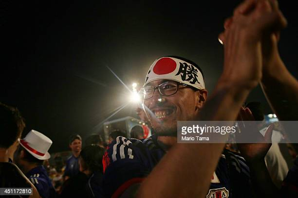 Japan supporters celebrate after their first goal against Colombia while watching at the FIFA Fan Fest on Copacabana Beach on June 24 2014 in Rio de...