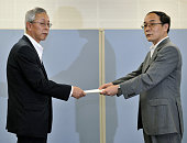 TOKYO Japan Takao Takahashi head of the Tokyo office of Hokkaido Electric Power Co receives a certificate for the completion of regular inspection of...