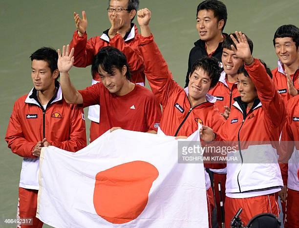 Japan team players Yuichi Sugita Go Soeda Kei Nishikori and Yasutaka Uchiyama hold the national flag in celebration following their Davis Cup tennis...