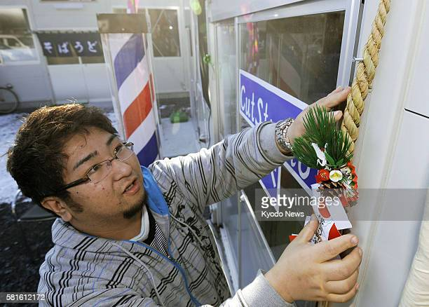 OTSUCHI Japan Tetsuro Abe puts up a New Year decoration around the entrance of his makeshift barber shop in the disasterhit town of Otsuchi in Iwate...