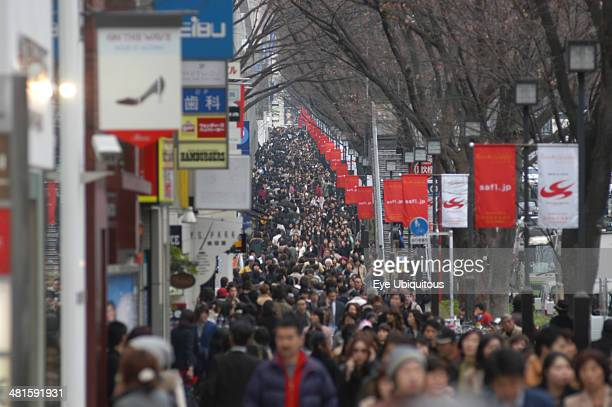 Japan Tokyo Harajuku Shoppers crowd on the busy Omotesandodori street a row of trees along the road and banners on the lampposts