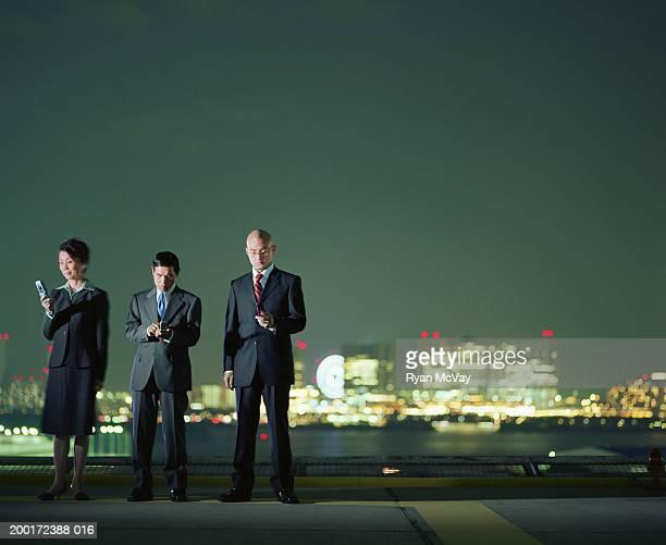 Japon, de Tokyo et Odaiba, trois hommes d'affaires avec téléphone portable sur le toit,