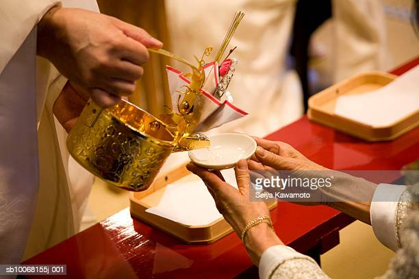 Japan, Tokyo, priest pouring liquid into bowl at wedding celebration, mid section, close up