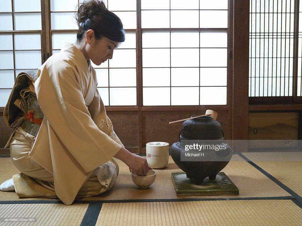 Japan, Tokyo, woman kneeling on floor, preparing tea, side view