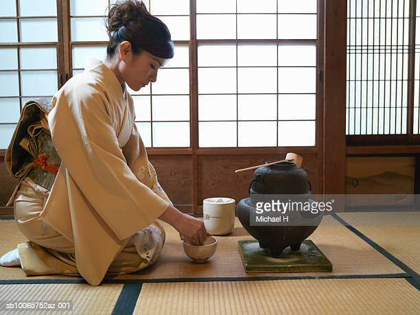 Japan, Tokyo, woman kneeling on floor, preparing tea, side view