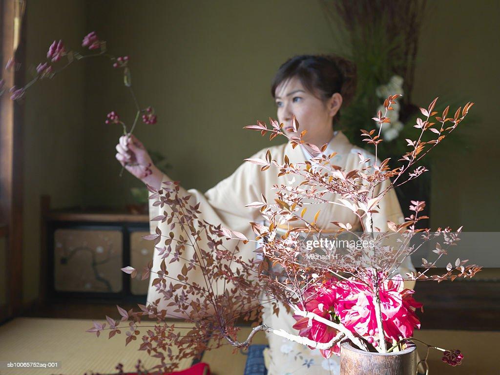 Japan, Tokyo, woman wearing kimono arranging flowers : Stock Photo