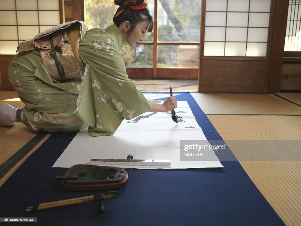 Japan, Tokyo, woman writing calligraphy, side view