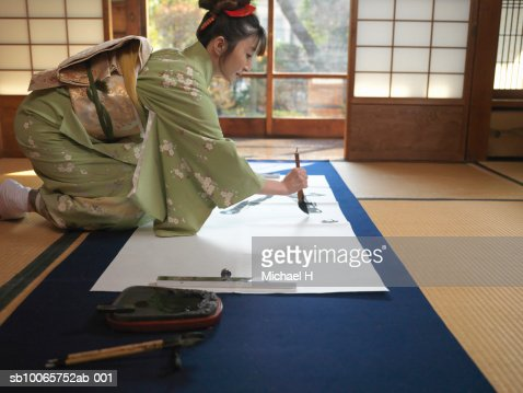 Japan, Tokyo, woman writing calligraphy, side view