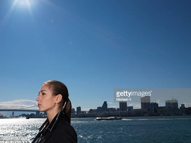 Japan, Tokyo, young businesswoman and cityscape, side view