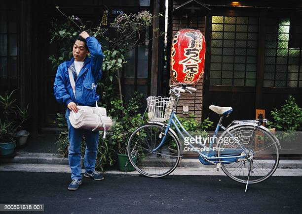 Japan, Tokyo young man delivering newspapers in street by bicycle