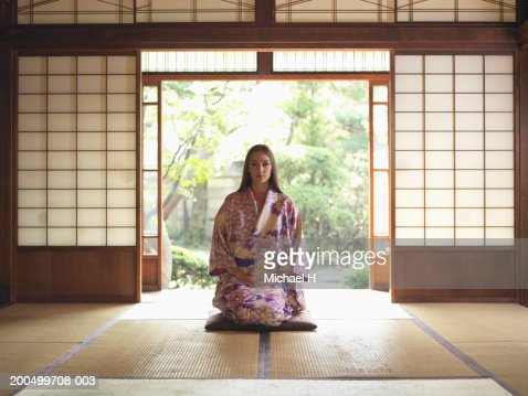 Japan, Tokyo, young woman in kimono kneeling on tatami mat, portrait