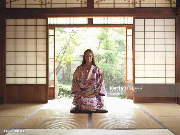 Japan, Tokyo, young woman in kimono kneeling on tatami mat, portrait