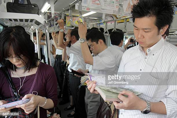 Japan Tokyo Yurakucho JR Yurakucho Station Yamanote Line Asian man woman crowded standing commuters train car strap holders read