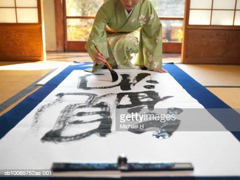 Japan, Tokyo,woman wearing kimono writing calligraphy on large piece of paper