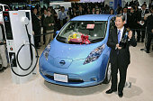 TOKYO Japan Toshiyuki Shiga chief operating officer of Nissan Motor Co holds the trophy while standing beside the Leaf electric vehicle at the Tokyo...