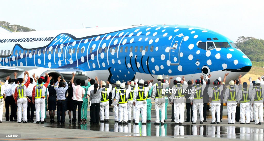 Japan Transocean Air staffs see off the first flight to Naha, which whale shark is drawn on the aircraft, at New Ishigaki Airport on March 7, 2013 in Ishigaki, Okinawa, Japan. The new airport has 2,000 meters long runway, 500 meters longer than former airport, expecting the increasing number of direct flights from Tokyo and Osaka.