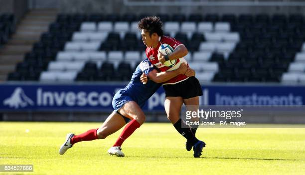 Japan wing Kanzo Nakahama is tackled by France's Mathieu Belie during the Invesco Perpetual Junior Rugby World Cup match at Liberty Stadium Swansea